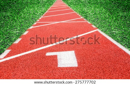 Start track. Lanes 1 number one on red racing track and grass background.
