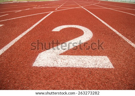 Start track number 2 on red running track. - stock photo