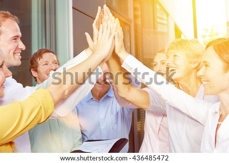 Start-up business team giving High Five with their hands in summer - stock photo