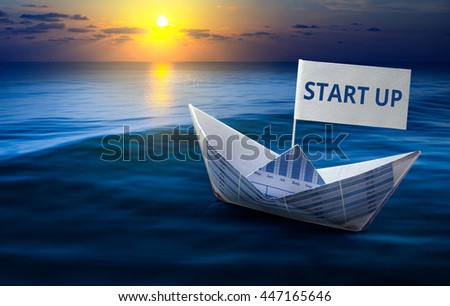 Start up word with boat made from business paper graph on sea and sun light.For business Start up  and financial concept ideas. - stock photo