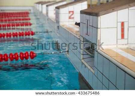 Starting blocks and lanes in a swimming pool. Edge of indoors sport swimming pool. Starting platforms with numbers for swimming races and competitions. Sport and health concept - stock photo