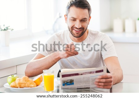 Starting day from good news. Handsome young man reading newspaper and smiling while drinking coffee and having breakfast in the kitchen - stock photo