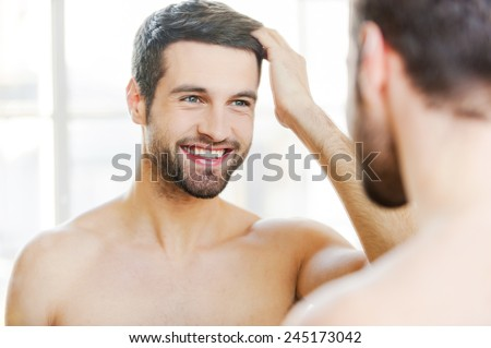 Starting new day with smile. Handsome young man touching his hair with hand and smiling while standing in front of the mirror - stock photo