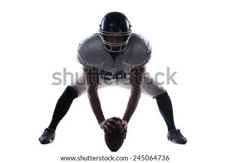 Starting the game.  American football player getting ready before starting the game while standing against white background  - stock photo