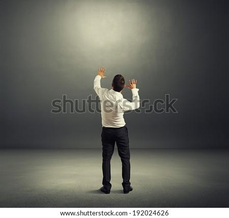 startled man in empty dark room - stock photo