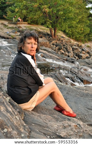 Startled woman sitting near a waterfall