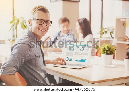 Startup business. Smiling and cheerful young creative man working with a help of laptop with his colleagues discussing something in a background - stock photo