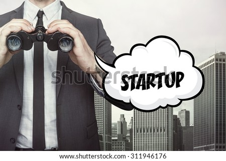 Startup text on speech bubble with businessman holding binoculars on city background - stock photo