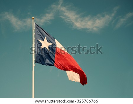 State flag of Texas against blue sky. Vintage filter effects. - stock photo
