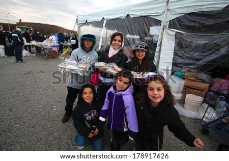 STATEN ISLAND, NEW YORK CITY - NOVEMBER 4 2012: Volunteers & national guard assembled at New Dorp High School to render aid to people recovering from Hurricane Sandy. Young volunteers pose before tent - stock photo