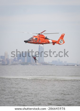 STATEN ISLAND, NY - MAY 24 2015: A Coast Guard rescue swimmer waves when hoisted by line into a US Coast Guard MH-65 Dolphin helicopter for a Search and Rescue demonstration for Fleet Week 2015. - stock photo