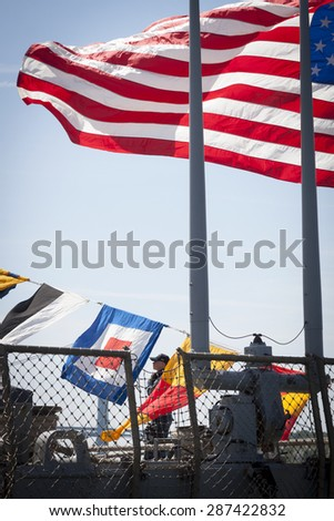 STATEN ISLAND, NY - MAY 24 2015: Armed security personnel standing under the American flag flying from the stern of guided-missile destroyer USS Barry (DDG 52) at Sullivans Pier during Fleet Week NY. - stock photo
