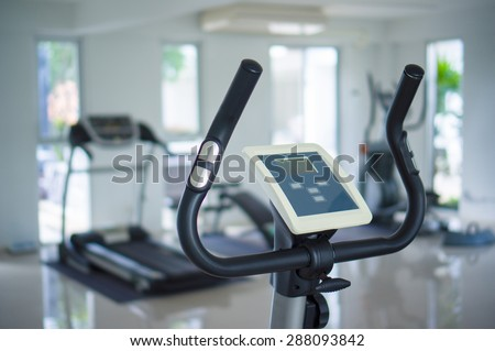 Stationary bicycle standing in a fitness gym - stock photo