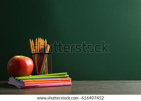 Stationery And Apple On Chalkboard Background