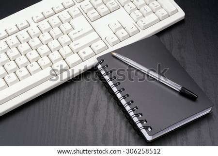 Stationery and computer keyboard on the black desk - stock photo