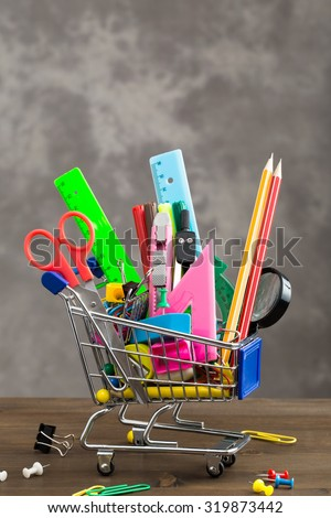 Stationery items in shopping trolley on table vertical  - stock photo
