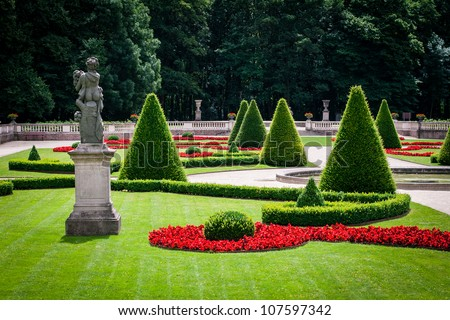 Statue and clipped trees and bushes in a classical park - stock photo