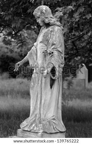 Statue in graveyard - stock photo