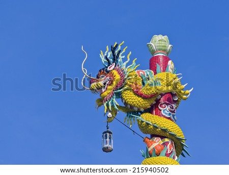 Statue of a dragon wrapped around a pole with blue sky background. - stock photo