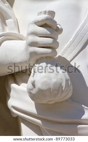 statue of a man carrying a purse full of coins (17 century) - stock photo