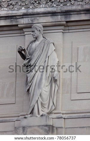 Statue of a man in toga reading a scroll on the roof of the Brooklyn Museum