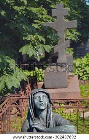 Statue of a mourning woman in cemetery - stock photo