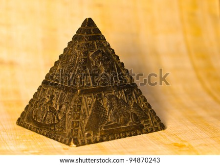 Statue of a stone pyramid with representations of typical egyptian scenes. Papyrus paper background, selective depth of field. - stock photo
