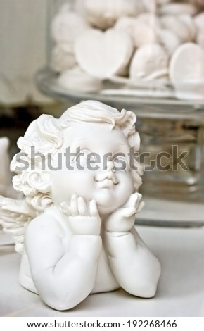 Statue of a white child angel, with heart candies in the back ground. Love concept. Useful for celebrations like wedding, anniversary, baptism. Clipping path of the angel included - stock photo