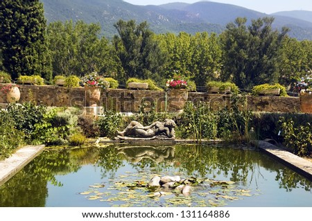 statue of a woman dozing on the banks of a picturesque pond in the Lourmarin Castle ( chateau de lourmarin ), Provence, Luberon, France - stock photo