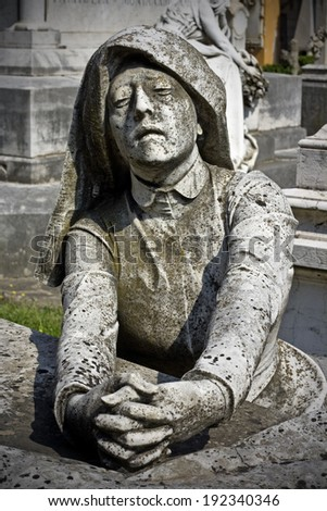 Statue of a woman praying on top of a tomb - certosa , bologna - stock photo