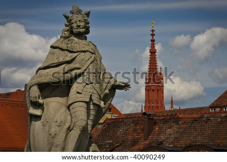 Statue of an ancient king with  cathedral in background in Wurzburg, Germany - stock photo