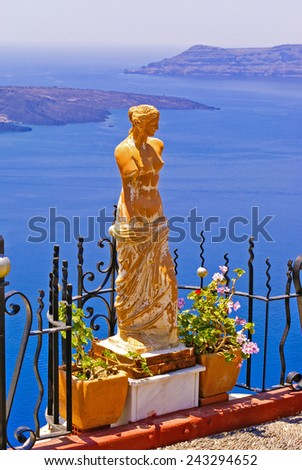 Statue of Aphrodite in Santorini, Greece, Therasia in the background - stock photo