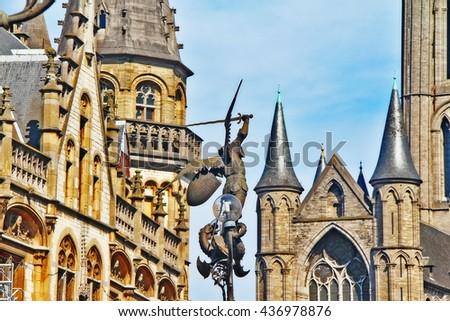 Statue of Archangel Michael slaying Dragon on St. Michael Bridge (Sint-Michielsbrug) with old Post office and Saint Nicholas Church (Sint-Niklaaskerk) in background, Ghent (Gent), Belgium - stock photo