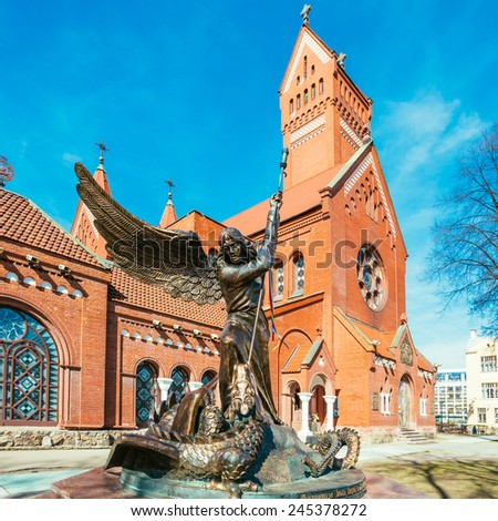 Statue of Archangel Michael with outstretched wings, thrusting a spear into a dragon before the Catholic Church of St. Simon and St. Helena. Red Church on Independence Square in Minsk, Belarus - stock photo
