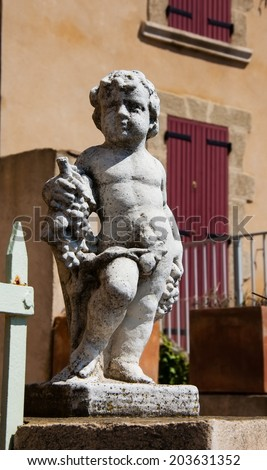 Statue of Bacchus (Dionysus) with grapes in his hands. Garden sculpture and old stone house with maroon wooden shutters at backgrounds. (Chateauneuf du Pape, Provence, France) - stock photo