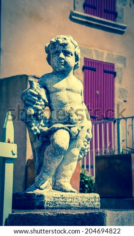 Statue of Bacchus (Dionysus) with grapes in his hands. Garden sculpture and old stone house with violet wooden shutters at background. Chateauneuf du Pape, Provence, France. Aged photo.  - stock photo