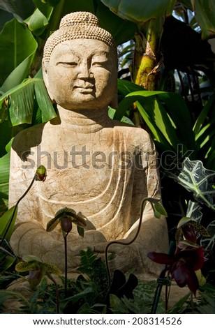 statue of Buddah in a shady garden corner - stock photo