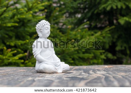 Statue of Buddha - peaceful mind. White deity on blur green background. Meditate concept. - stock photo