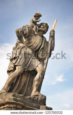 Statue of Child Christus at the shoulder of saint Christopher, Charles Bridge, Prague - stock photo