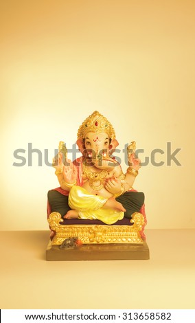Statue of colorful Ganesha idol on yellow background. Greeting card cover template. - stock photo