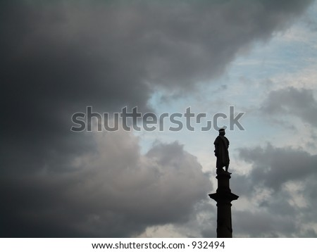 Statue of Columbus against a dramatic sky