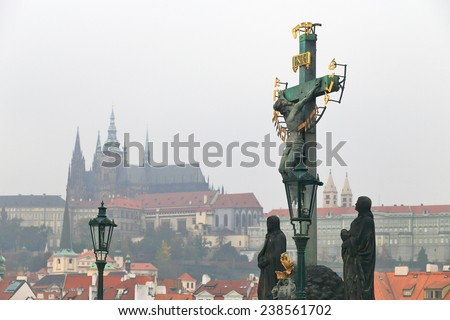 Statue of crucified Jesus on Charles bridge with St Vitus Church in the background in cloudy autumn day, Prague, Czech Republic - stock photo