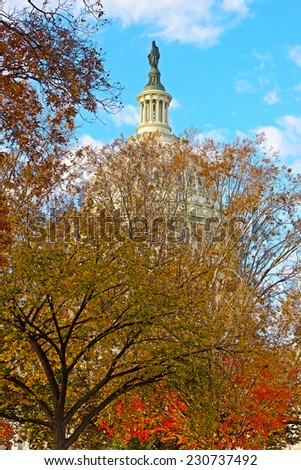 Statue of Freedom on top of US Capitol Building in Washington DC. The dome of US Capitol building behind colorful autumn foliage. - stock photo