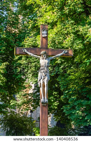 Statue of Jesus Christ crucified. In the very background the Church of the Immaculate Conception of the Blessed Virgin Mary in Katowice, Silesia region, Poland. - stock photo