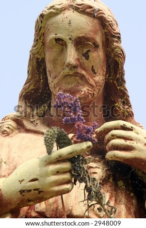 Statue of Jesus with Flower Offerings - stock photo