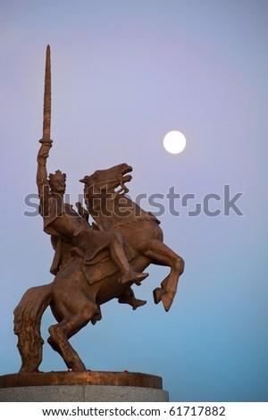 statue of King Svatopluk with full moon in the background, Bratislava, Slovakia - stock photo