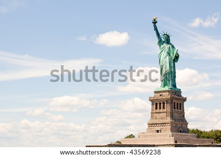 Statue of liberty against blue New York sky - stock photo