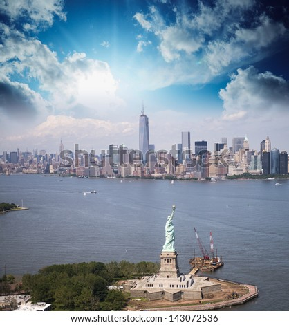 Statue of Liberty and Manhattan skyline. Spectacular helicopter view at sunset. - stock photo