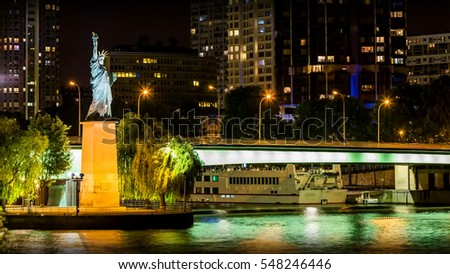Statue of liberty in Pont de Grenelle view at night, city of Paris, France