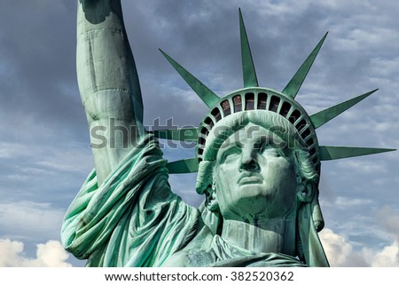 Statue of liberty on cloudy sky background